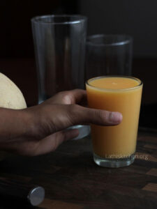 A hand holding a glass of cantaloupe smoothie.